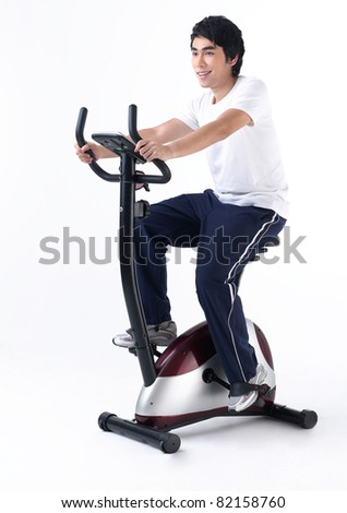 A young man cycling bicycle in a gym - stock photo