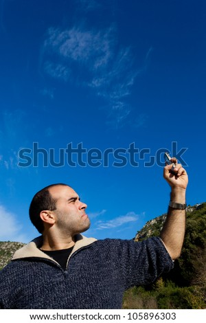 A young man displeased by getting no signal on his phone - stock photo