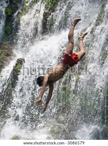 A young man dives off a waterfall makes it look like he is plunging to his death. - stock photo