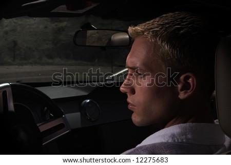 A young man driving a car at sundown - stock photo