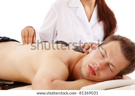 A young man enjoying hot stone therapy on white - stock photo