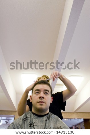 A young man getting his hair cut by a hairdresser at the beauty salon.  Plenty of copy space with this unique perspective. - stock photo