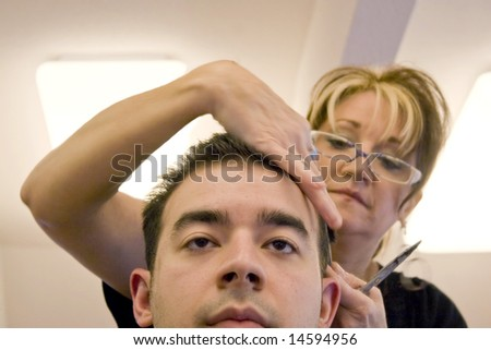 A young man getting his hair cut by a hairdresser at the salon - stock photo