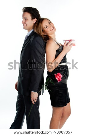 A young man gives a beautiful young woman, a flower in honor of the holiday - stock photo