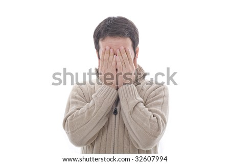a young man his hidding his face with both hands - stock photo