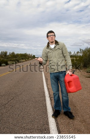 A young man hitchikes to catch a ride for some gasoline. - stock photo