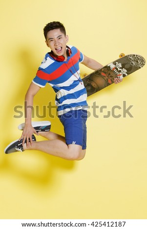 A young man holding a skate - stock photo