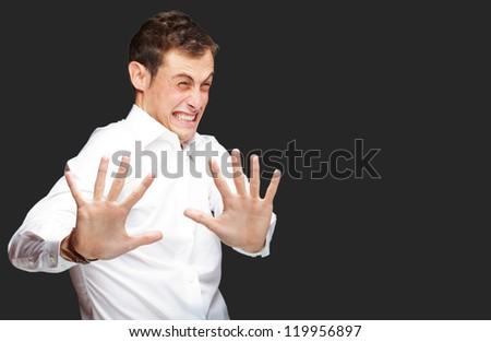 A Young Man Holding His Hands Out In Fear On Black Background - stock photo