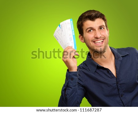 A Young Man Holding Tickets On Green Background - stock photo