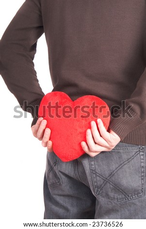 A young man holds a heart shaped pillow behind his back which he gives as a present to his girlfriend for valentines day. Isolated over white. - stock photo