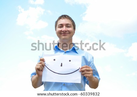 A young man holds a sheet of paper with a picture - stock photo