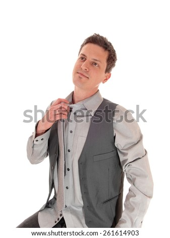 A young man in a grey shirt and tie and vest, taking his tie of,