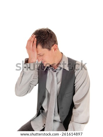 A young man in a grey shirt, tie and vest sitting isolated for white