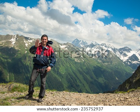 A young man in a jacket stands near the cliff and smiles on the background of the North Caucasus mountain range and cloudy sky - stock photo