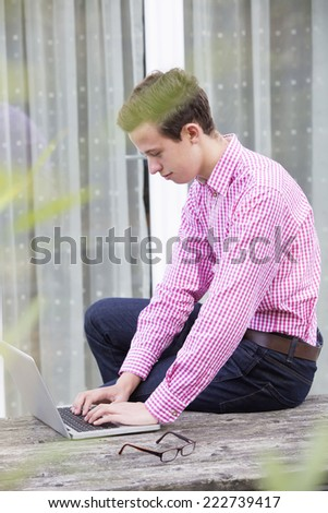 a young man in a red shirt sitting outside with a laptop - stock photo
