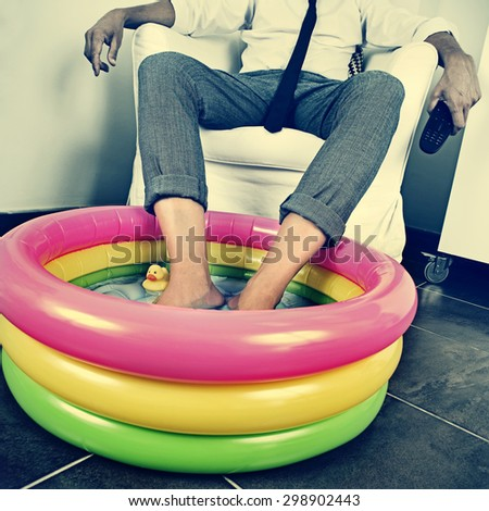 a young man in suit soaking his feet in an inflatable water pool indoors, with a dramatic effect, depicting the concept of staying at home on vacation - stock photo