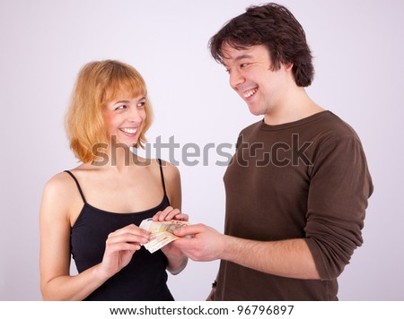 A young man is giving his girlfriend some money - stock photo