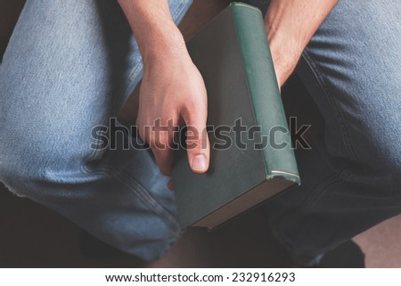 A young man is sitting and holding a big old book - stock photo
