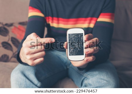 A young man is sitting on a sofa and is pointing at a broken smart phone with a cracked screen - stock photo