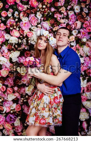 A young man is tenderly hugging a beautiful girl near a spring floral wall. - stock photo