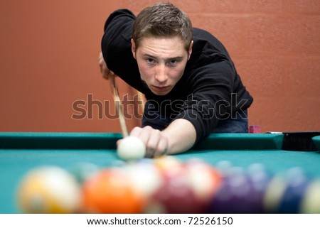 A young man lines up his shot as he breaks the balls for the start of a game of billiards. Shallow depth of field. - stock photo
