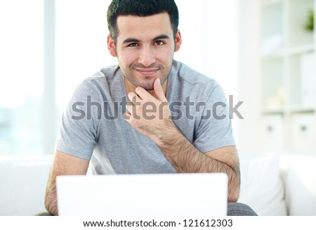 A young man looking at camera while working with laptop - stock photo
