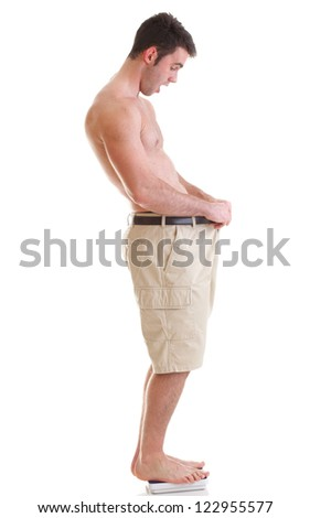 A young man looking down at his pants when he was fat. lost some weight Isolated on white. - stock photo