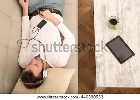 A young man lying on the sofa listening to music with some headphones and a smartphone. - stock photo