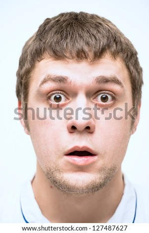A young man makes a face to face - stock photo