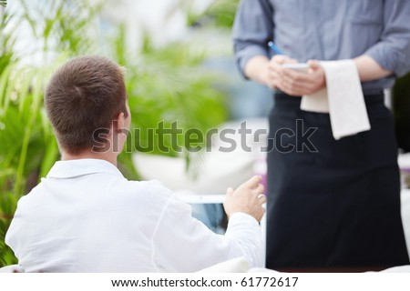 A young man makes a restaurant reservation - stock photo