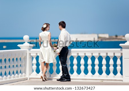A young man meets the open air with the girl on a background of summer sea landscape - stock photo