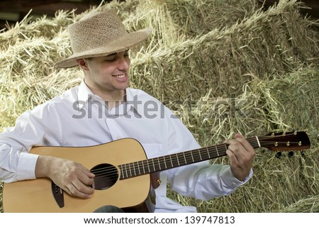 A young man playing country and western tunes on his guitar in the barn while sitting on bales of hay. - stock photo