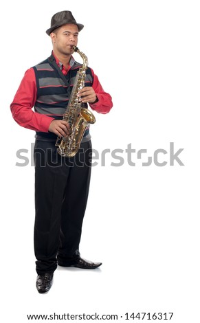 A young man plays his saxophone whilst standing upright. - stock photo