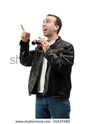 A young man pointing at some blank space while holding a set of binoculars, isolated against a white background - stock photo