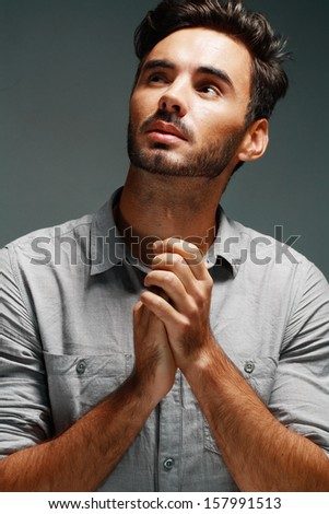 A young man prays over studio grey background - stock photo