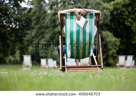 A young man relaxing on a deckchair in St James Park, holding a guidebook - stock photo