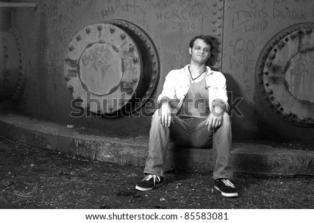 A young man resting against an iron wall - stock photo