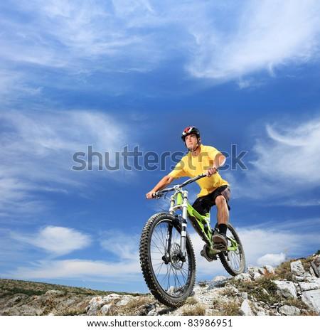 A young man riding a mountain bike outdoor - stock photo