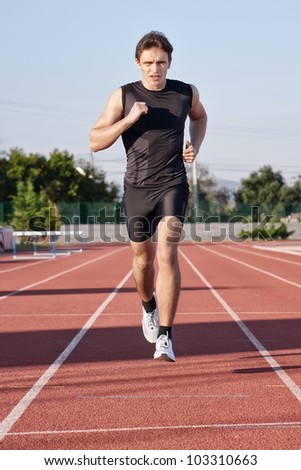 A young man run a hundred meters on the treadmill. - stock photo