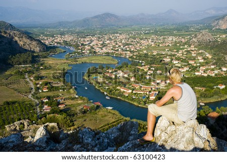 A young man, sat looking out over a view in Turkey - stock photo