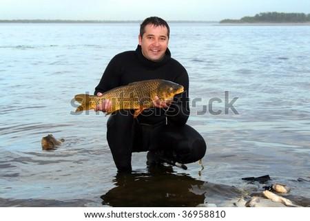 A young man scuba diver spear fish a carp - stock photo