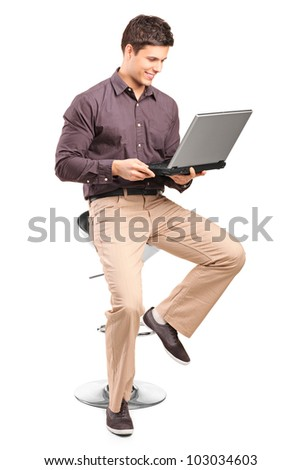 A young man sitiing on a high chair and working on a laptop isolated on white background - stock photo