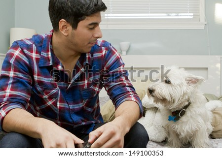 A young man sits in his bedroom with his dog. - stock photo