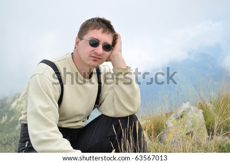 A young man sits on a hilltop and looking thoughtfully into the distance - stock photo
