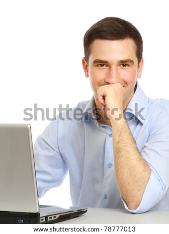 A young man sitting in front of a laptop - stock photo