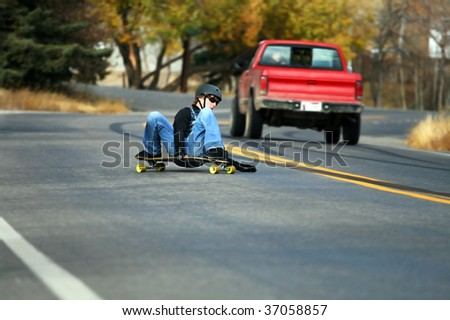 A young man skateboards past a truck on a steep residential road. - stock photo