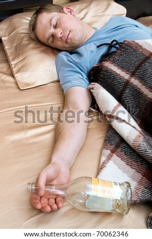 A young man sleeping on the couch with a bottle of whiskey - stock photo