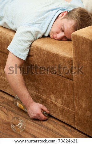 A young man sleeping on the couch with a bottle of wiskey - stock photo