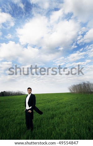 A young man standing in a field wearing a tuxedo. - stock photo