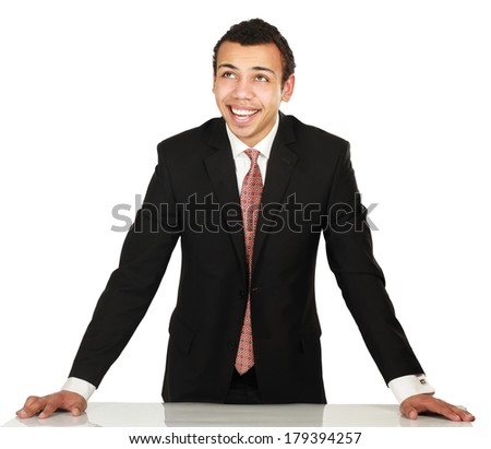 A young man standing near desk, isolated on white background - stock photo